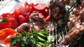 Deliver from the grill on a plate of vegetables delicious juicy pieces of meat. 4k, 3840x2160. HD stock video footage