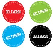 DELIVERED text, on round wavy border stamp badge. Stock Photography