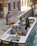 Deliveries in Venice. Venice, Italy, Oct 24 2011: Water taxi and workboat navigating narrow canal in Venice.  All manner of supplies and people transportation Stock Images