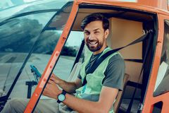 Cheerful good-looking man sitting on the front seat of the helicopter stock photography