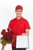 Delivering flowers. Cheerful young deliveryman stretching out a Royalty Free Stock Photos