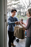 Delivering Groceries To The Elderly. Teenage boy is delivering some groceries to an elderly woman. He is handing her a shopping bag at her front door royalty free stock image