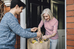 Delivering Groceries To The Elderly. Teenage boy is delivering some groceries to an elderly woman. He is handing her a shopping bag at her front door stock images
