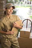 Delivering package. Young woman courier delivering shipment or package at door stock image