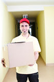 Delivering packages. Your handsome delivery man during his work Stock Photo