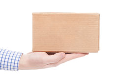 Delivering of parcel to the customer (only one hand and parcel seen) - studio shot Royalty Free Stock Images