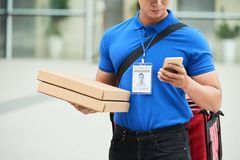 Delivering pizza. Crooped image of delivery man with two boxes with pizza checking address in smartphone application Royalty Free Stock Photo