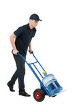 Delivering water. Cheerful young going carrying a hand truck wit. H water jug on it while isolated on white Stock Images