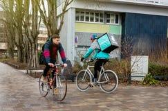 Deliveroo骑自行车的人在努力工作的雨天交付准时foo 库存图片