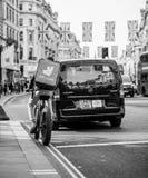 Deliveroo kurir på cykeln på rött ljus Regent Street Arkivbild