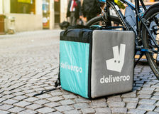 Deliverro在一辆自行车附近的货物箱子在餐馆前面 库存图片