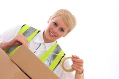 Delivery. Image of a  delivery woman at work with a smile sticking a box together Stock Photography