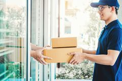 Free Delivery Asian Man Service With Boxes In Hands Standing In Front Of Customer`s House Doors Royalty Free Stock Photo - 144068515