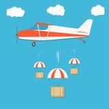 delivery Avion avec des paquets de boîte de parachute sur le fond de ciel bleu Photographie stock libre de droits