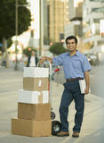 Delivery of Boxes. Portrait of an Hispanic delivery man on city sidewalk with hand truck full of boxes to deliver Royalty Free Stock Photography