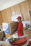 Delivery boy With Cardboard Box Moving Into New House. Portrait of a delivery men with cardboard box moving into new house Royalty Free Stock Image