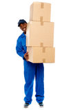 Delivery boy carrying heavy boxes Royalty Free Stock Images