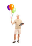 A delivery boy delivering balloons Stock Images