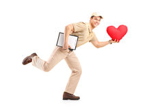 Delivery boy delivering heart shaped object. A delivery boy in a rush delivering red heart shaped object isolated against white background Royalty Free Stock Image