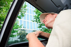 Delivery Boy Driving A Van. A delivery person is driving his van and looking up at a skyscraper Stock Images
