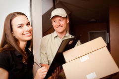 Delivery Boy Handing Over Some Packets Royalty Free Stock Photos
