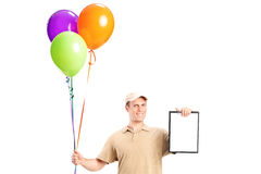 Delivery boy holding balloons and a clipboard Royalty Free Stock Image