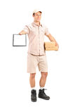Delivery boy holding a packet and giving a clipboard for signatu. Full length portrait of a delivery boy holding a packet and giving a clipboard for signature Royalty Free Stock Photos