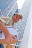 Delivery Boy Standing In Front Of Modern Buildings. A smiling delivery person is standing in front of modern buildings, holding some packets Royalty Free Stock Photos