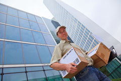 Delivery Boy Standing In Front Of Modern Buildings. A smiling delivery person is standing in front of modern buildings, holding some packets Stock Images