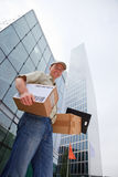 Delivery Boy Standing In Front Of Modern Buildings. A smiling delivery person is standing in front of modern buildings, holding some packets Stock Photo