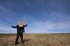 Delivery businessman. Businessman with an box on his head at the field royalty free stock images