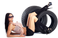 Delivery car wheels. Young sexy woman with laptop and headset sitting on the car wheels, isolated on white Stock Image