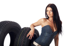 Delivery car wheels. Young sexy woman with laptop and headset sitting on the car wheels, isolated on white Stock Photo