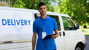 Delivery company worker filling report, student part-time job, fast shipment. Stock photo royalty free stock photography