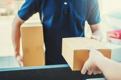 Delivery concept Asian Man hand accepting a delivery boxes from professional deliveryman at home.  stock image