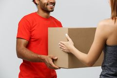 Delivery Concept - Handsome African American delivery man giving  package to homeowner. Isolated on Grey studi. Delivery Concept - Handsome African American Stock Image
