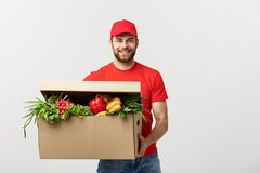 Delivery Concept: Handsome Caucasian grocery delivery courier man in red uniform with grocery box with fresh fruit and. Vegetable royalty free stock image
