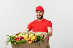 Delivery Concept: Handsome Caucasian grocery delivery courier man in red uniform with grocery box with fresh fruit and. Vegetable stock image