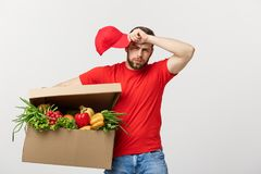 Delivery Concept: Handsome delivery man is holding a heavy grocery box isolated over grey background. Delivery Concept: Handsome delivery man is holding a heavy Stock Images