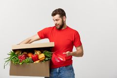 Delivery Concept: Handsome delivery man is holding a heavy grocery box isolated over grey background. Delivery Concept: Handsome delivery man is holding a heavy Royalty Free Stock Image