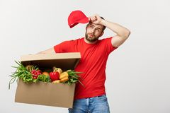 Delivery Concept: Handsome delivery man is holding a heavy grocery box isolated over grey background. Delivery Concept: Handsome delivery man is holding a heavy Stock Image
