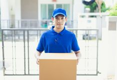 Delivery concept - Portrait delivery person in blue uniform hold. Ing cardboard box standing in front the home customers Royalty Free Stock Images