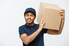 Delivery Concept - Portrait of Serious African American delivery man showing silly aggressive expression with holding a. Box package. Isolated on Grey studio stock photos