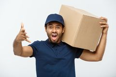 Delivery Concept - Portrait of Serious African American delivery man showing silly aggressive expression with holding a. Box package. Isolated on Grey studio Stock Photo