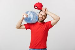 Delivery Concept: Portrait of smiling bottled water delivery courier in red t-shirt and cap carrying tank of fresh drink. Isolated over grey background royalty free stock photography