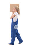 Delivery concept - side view of woman in blue workwear walking w Royalty Free Stock Photos