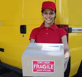 Delivery courier  delivering postal packages. Young delivery courier or mailman delivering postal packages Royalty Free Stock Photo
