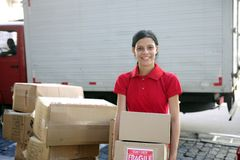 Delivery courier or mover delivering cardboards. Young delivery courier or mover delivering cardboards Royalty Free Stock Photo