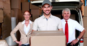 Delivery driver and business team smiling at camera