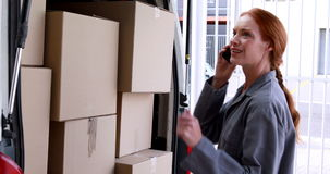 Delivery driver checking her load in the van Stock Image